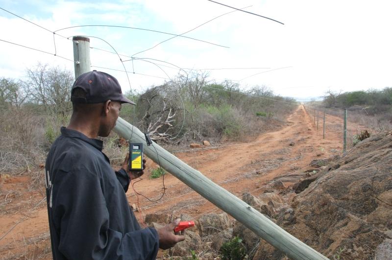 Ein Arbeiter kontrolliert den Elektrozaun in Ithumba